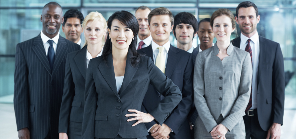 Happy asian businesswoman smiling at the camera with her hand on her hip and her colleagues in the background